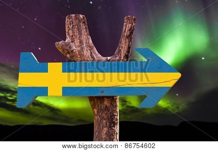 Sweden wooden sign with northern lights background