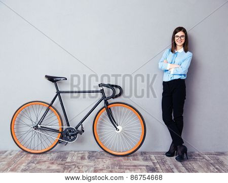 Full length portrait of a happy businesswoman with arms folded standing near bicycle. Wearing in blue shirt and glasses. Looking at camera