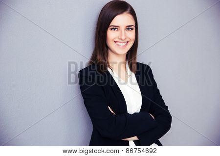 Happy young businesswoman with arms folded standing over gray background. Looking at camera
