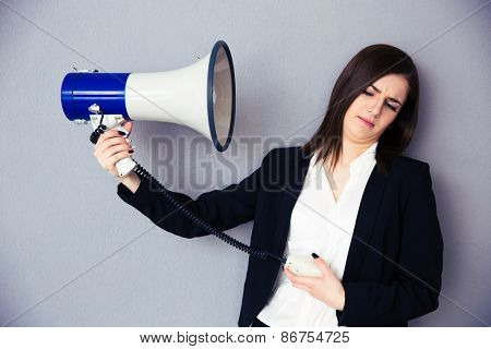 Young businesswoman points megaphone at herself over gray background