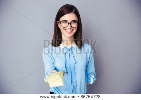 Smiling businesswoman giving money on camera over gray background. Wearing in blue shirt and glasses. Looking at camera