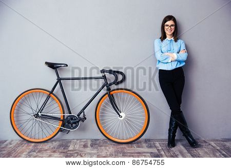 Cheerful young businesswoman with arms folded standing near bicycle. Looking at camera