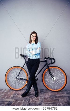 Smiling businesswoman with arms folded standing near bicycle. Looking at camera