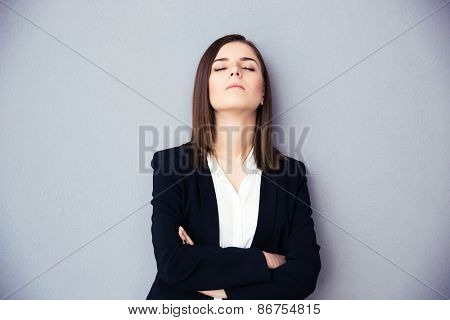 Young businesswoman with closed eyes and arms folded standing over gray background