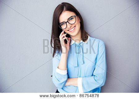 Happy businesswoman talking on the phone over gray background. Wearing in blue shirt and glasses. Looking at camera