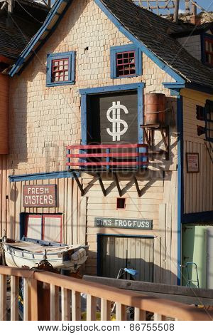 Old wooden building selling fresh oysters with a dollar sign in the window and a wooden picket fence in front
