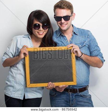 Happy Young Multiculture Couple Posing With Chalk Board