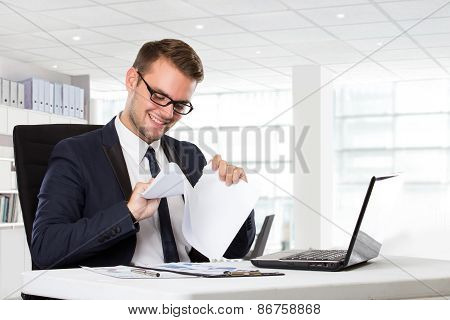 Young Businessman Checking Paper Beside In Front Of Laptop