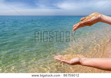 Female Hands Pouring Coral Sand On The Sea Background