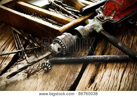 Old drill, box with drills on wooden background.