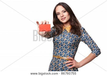 Smiling young woman in colorfull dress showing a card. Isolated on white