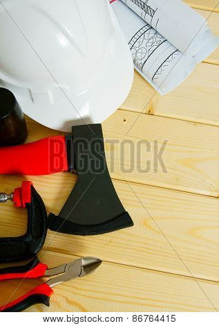 Drawings for building, axe, clamp and others tools on wooden background.