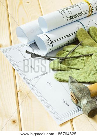 Repair work. Drawings for building, hammer and gloves on wooden background.