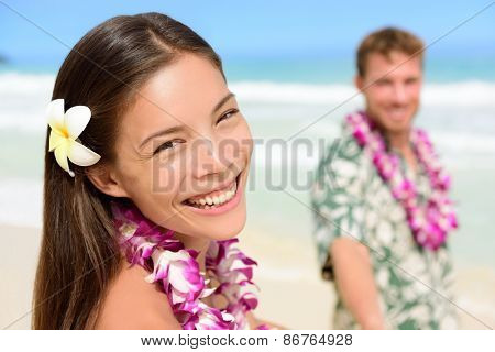 Happy Hawaii couple in Hawaiian lei, flower head and Aloha shirt. Portrait of a smiling Asian multiracial woman with Caucasian boyfriend on beach, multiethnic couple on summer travel vacations.