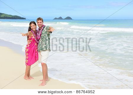 Portrait of couple of tourists happy standing on Hawaiian beach at their Hawaii vacation. Asian woman and Caucasian man wearing flower lei garland and Aloha clothing showing Shaka hand sign on travel.