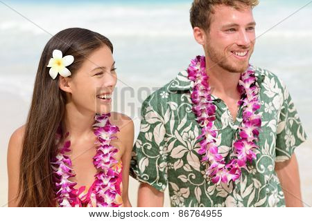 Happy Hawaii beach couple in Aloha Hawaiian shirt. Portrait of Asian woman and Caucasian man on beach walking with flower leis and typical attire for their wedding or honeymoon.