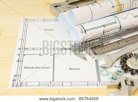 Drawings for building and metal working tools on wooden background.