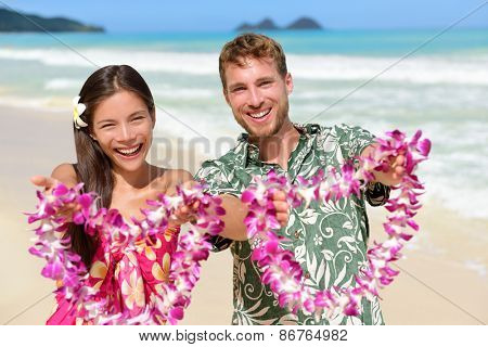 Welcome to Hawaii - Hawaiian people showing leis flower necklaces as a welcoming gesture for tourism. Travel holidays concept. Asian woman and Caucasian man on white sand beach in Aloha clothing.