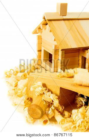 House construction. Joiner's works. The small wooden house, plane and shaving on white background.