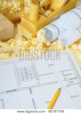 Woodworking. Drawings for building, small house and working tools on wooden background.