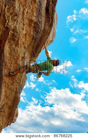 Rock climber climbing up a cliff