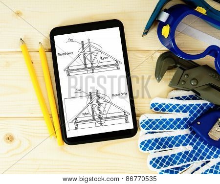 Tablet, drawings and working tools on a wooden background.