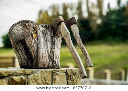 Two Ax, Hatchets In A Log On The Background Of Green Grass
