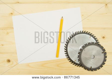 The Sheet of paper with pencil and circle saw on wooden background.