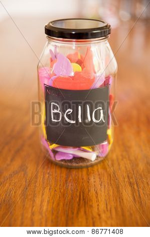 Image of a jar of gifts on an oak wood table