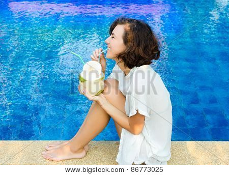 Woman drinking the coconut cocktail near the swimming pool