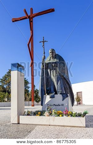 Sanctuary of Fatima, Portugal, March 07, 2015 - Statue of Pope John Paul II with the High-Cross and Basilica of Most Holy Trinity in background. Fatima is one of the most important Marian Shrines