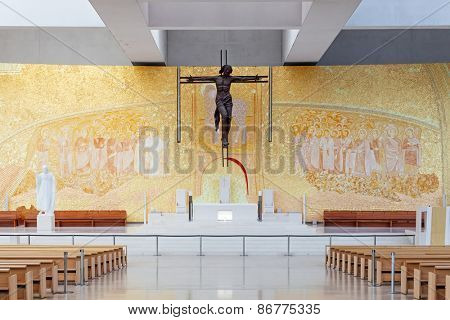 Sanctuary of Fatima, Portugal, March 07, 2015 - Basilica of Most Holy Trinity altar. Crucifix by Catherine Greene and Back Wall by Marko Ivan Rupnik. Fatima is a major Marian Shrine pilgrimage site
