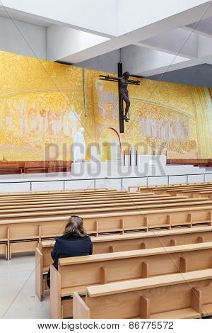 Sanctuary of Fatima, Portugal, March 07, 2015 - Faithful praying inside the modern Minor Basilica of Most Holy Trinity. Fatima is one of the most important pilgrimage locations for the Catholics