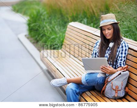 Young girl on a bench with a laptop