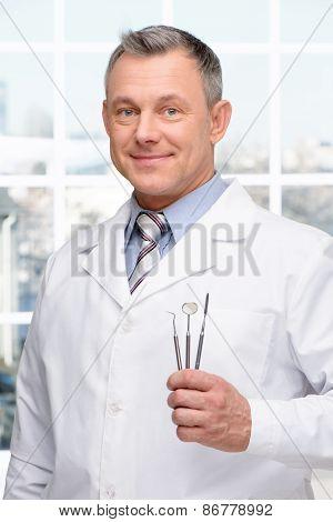 Dentist holding stomatologist tools