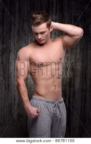 Young well formed man demonstrating muscles