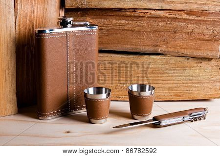 Hip Metal Flask, Cups And Knife On Wooden Background.