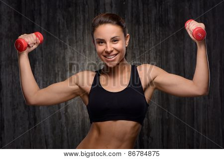 Smiling mixed race sporty woman holding dumbbells