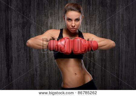 Mixed race sporty woman wearing boxing gloves