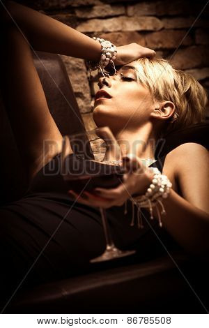 beautiful young woman lie holding glass of red wine in hand, side view, close up, indoor shot