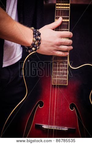 man hand on old acoustic guitar indoor shot, focus on hand