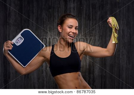 Smiling mixed race sporty woman holding weighs and measuring tape