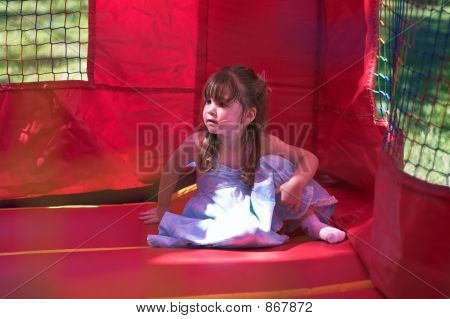Young Girl Sitting In An Inflatable Bouncy