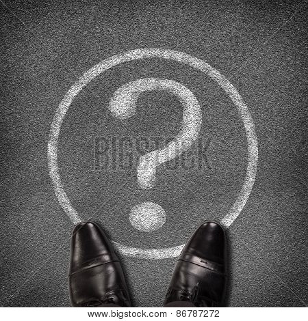 Shoes standing on asphalt road with circle and question mark