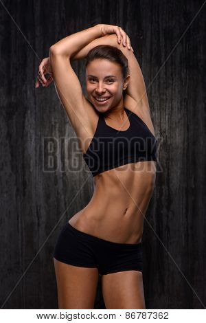 Smiling mixed race sporty woman demonstrating her figure