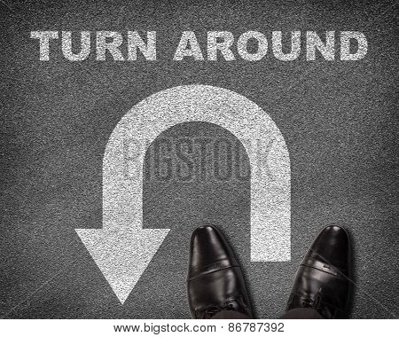 Shoes standing on asphalt road with U-turn sign and text turn around