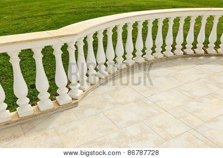 Fancy marble railing on ceramic tile patio with lawn