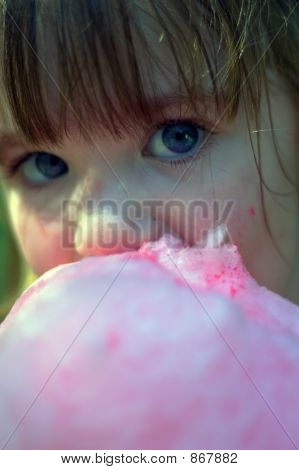 Close Up Of Young Girl Eating Cotton Candy