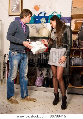 Shop Assistant Showing White Bag To Beautiful Girl