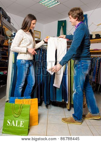 Shop Assistant Showing White Jeans To Beautiful Gir